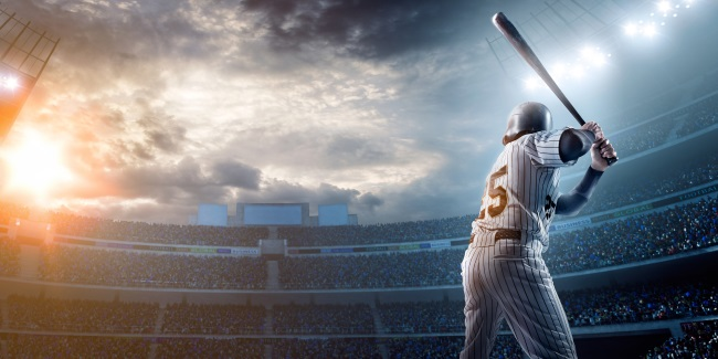 Baseball player swinging for the fences in stadium.
